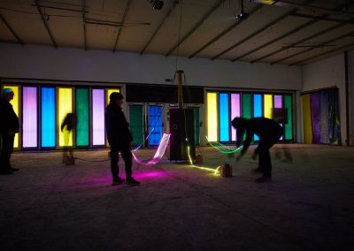 A group of people in silhouette interact with a illuminated installation. There are coloured panels in the background.
