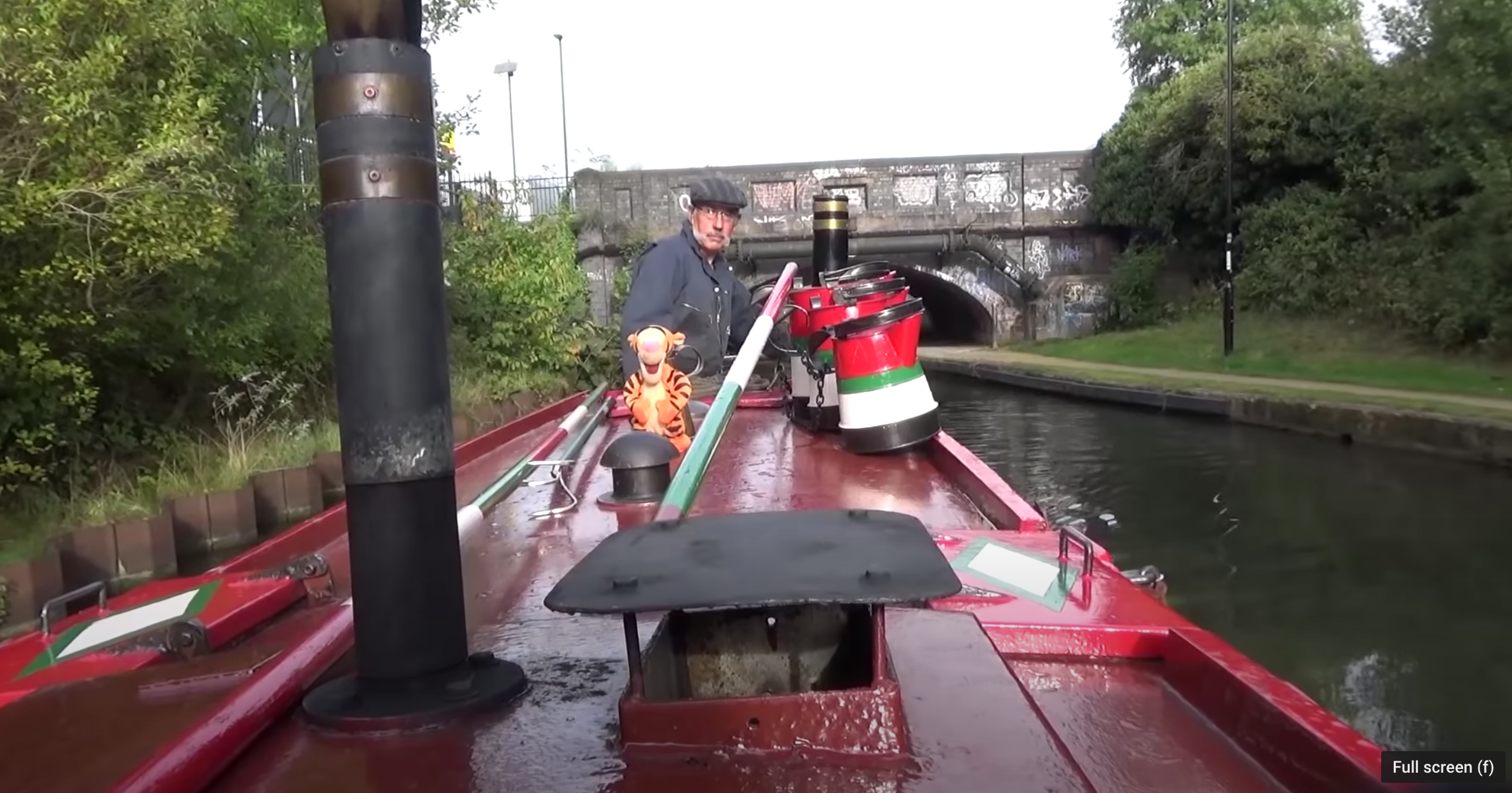 A man taking his red boat out on the canal, heading towards the bridge. An image from Alan Van Wijgerden's film titled, 'Coal, gas and diesel'