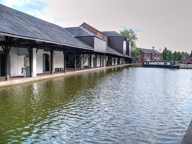 Canal warehouses sitting alongside the canal river with a boat at the end. The warehouse became listed as a Grade II building.